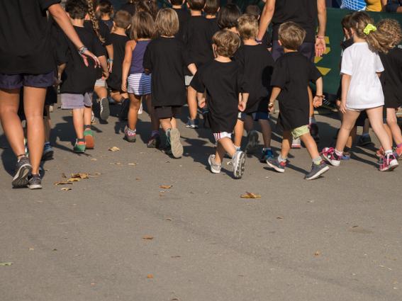 children running with their teacher on sports day