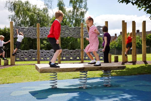 school children on a playground wobble board