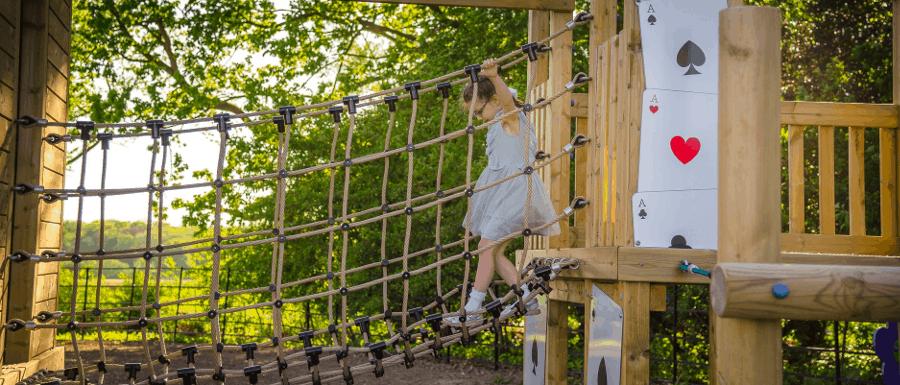 girl using new playground rope bridge