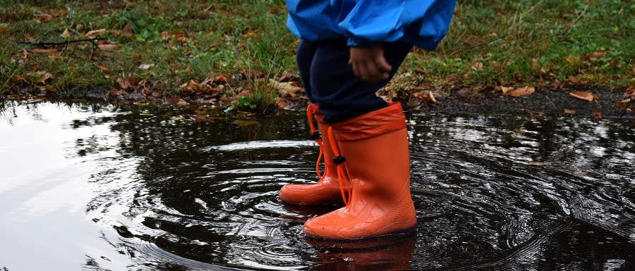 child in red wellington boots playing in the rain and puddles
