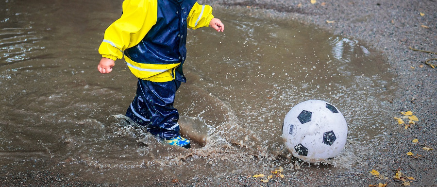 child playing in the rain with a football