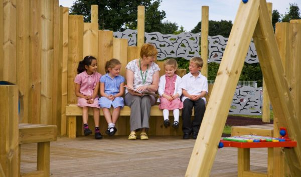 teacher and pupils using outdoor classrooms for schools