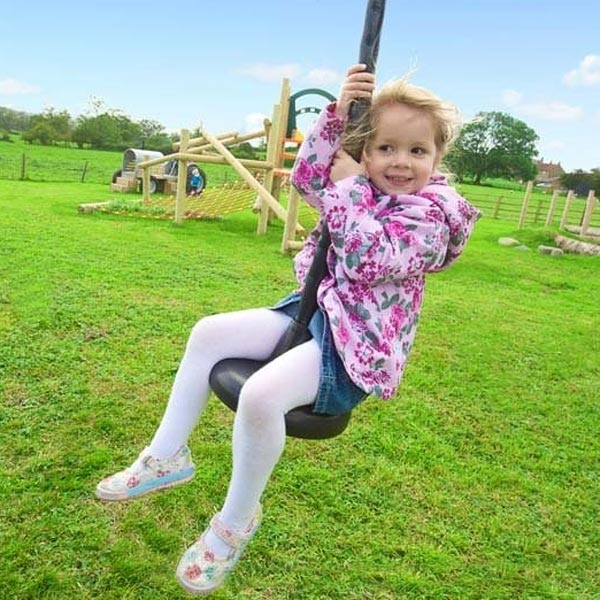 young girl on a playground zipline