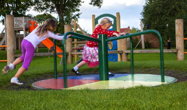 two girls enjoying a playground roundabout