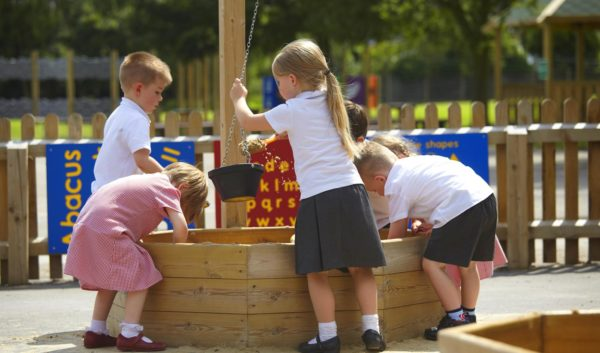 school children using sand playground equipment