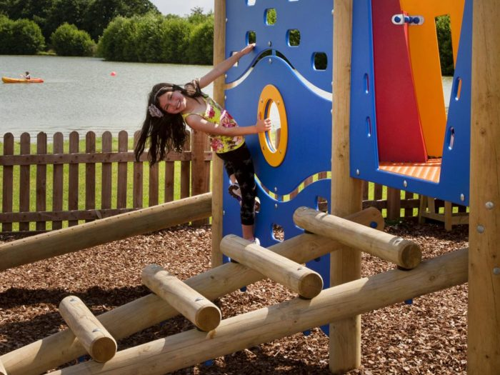young girl on Allerthorpe Lakeland Park playground climbing equipment