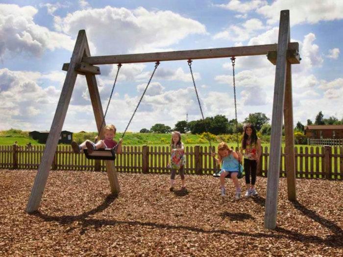 children using wooden playground swings
