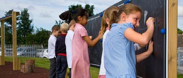 children enjoying creative social play on outdoor black boards