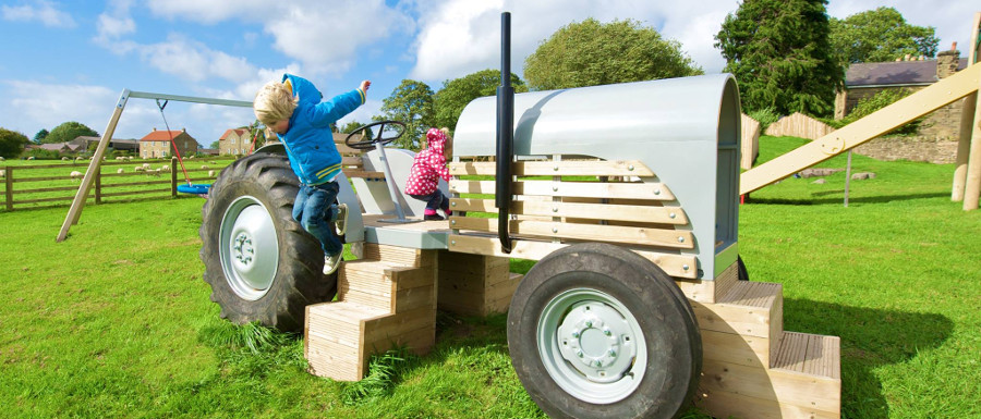 children using a role play tractor in their playground