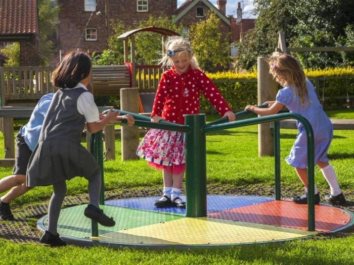 children on a playground roundabout