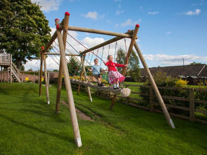 children using a community playground large rope swing