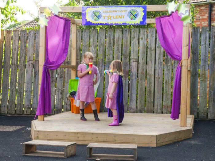 children using an outdoor playground stage