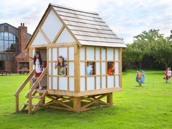 children inside a mock Tudor playhouse