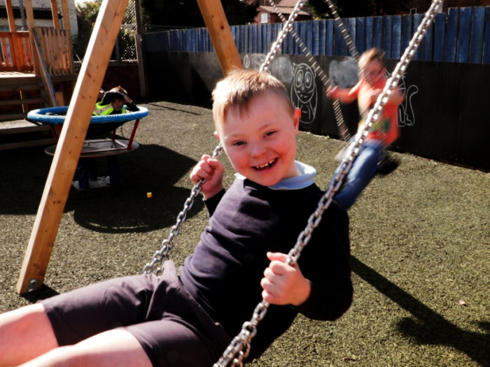 child on a swing in an inclusive playground
