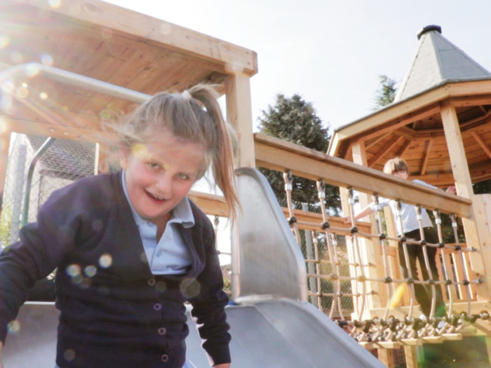 girl using inclusive playground equipment