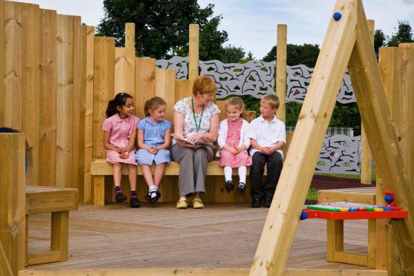 teacher reading to school children in a playground amphitheatre