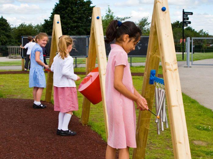 school children using musical playground equipment