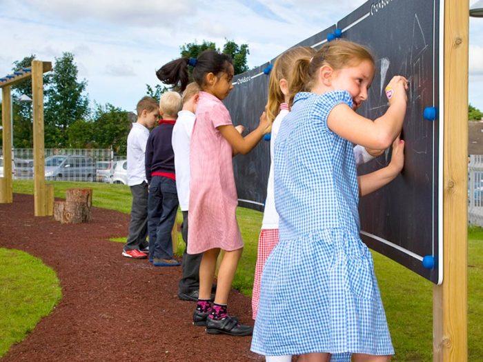 school children using a school playground blackboard