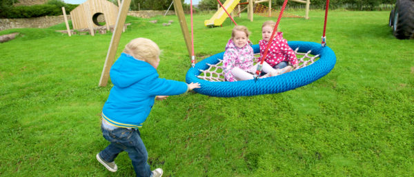 children in a basket swing while another pushes