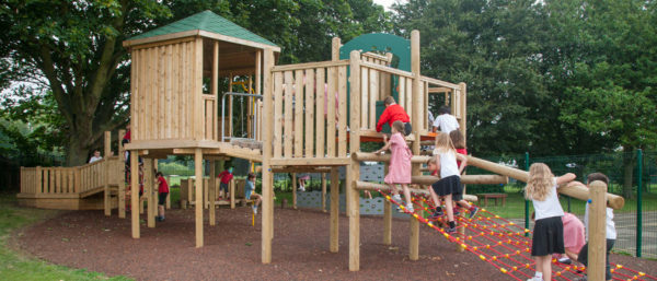 children playing on climbing equipment above playground safety surfacing
