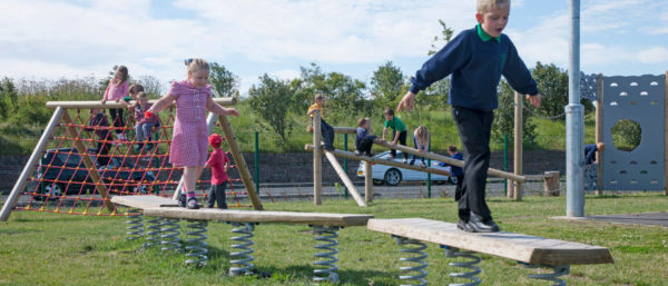 children playing on wobble boards and climbing equipment