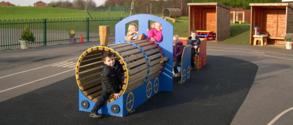 children using a role play train in their playground