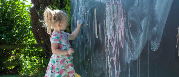 girl using a playground blackboard during free play