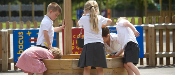 school children free playing with a school sand pit