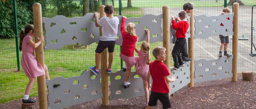 children using a playground climbing traverse wall