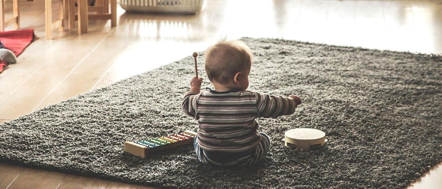 young child using musical instruments at home
