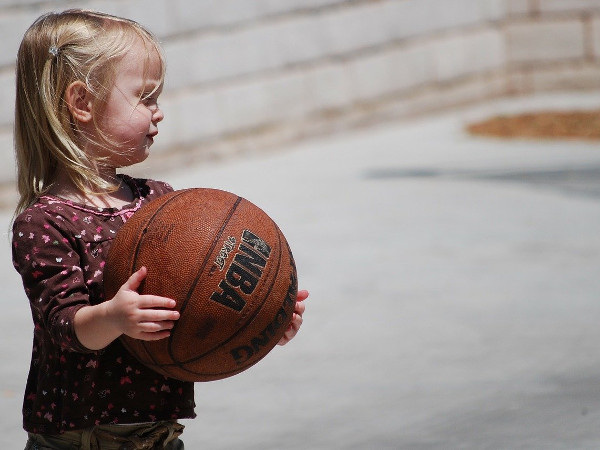 girl holding a basketball as part of a home obstacle course