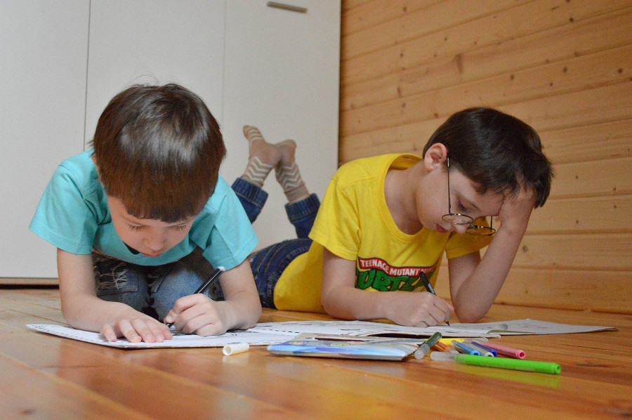 siblings colouring together on the floor