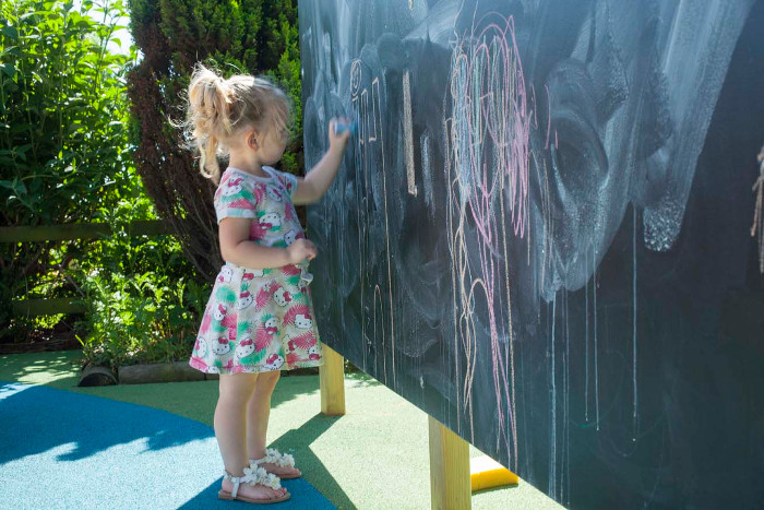 girl drawing on a playground chalkboard