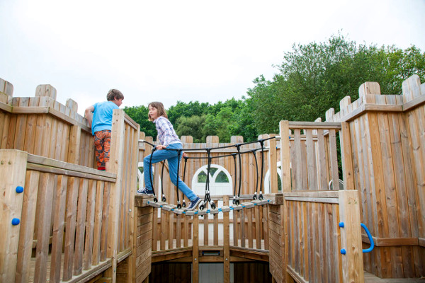children playing together on playground climbing equipment
