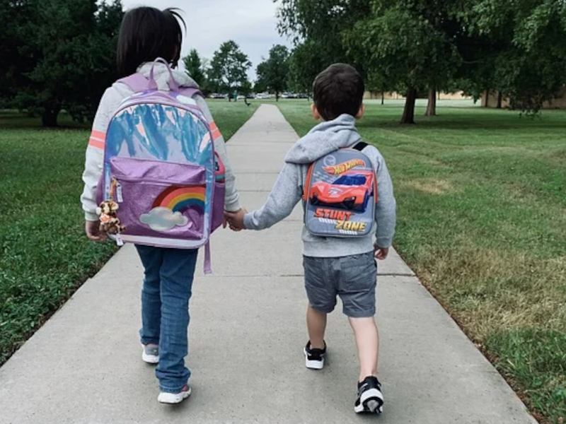brother and sister holidng hands and walking to school