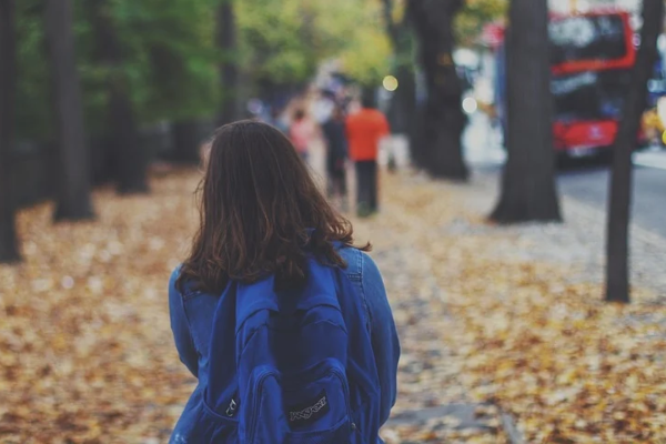 child with a backpack walking to school