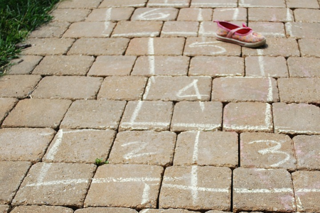 Hopscotch grid with a child's shoes on it