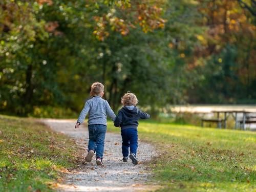 siblings running in a park