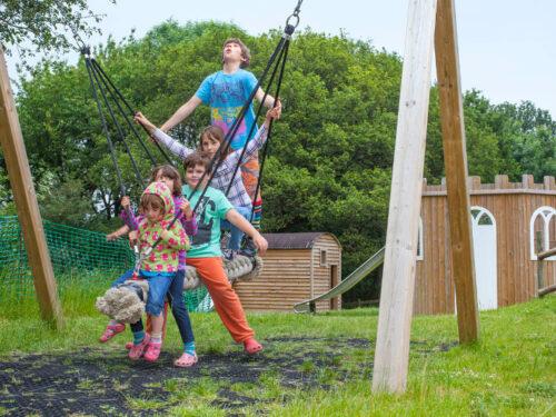 Children using a log swing