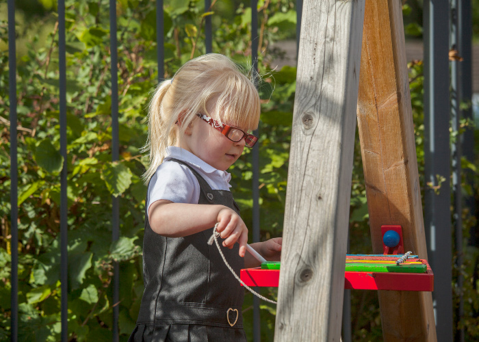 school girl playing on an playground xylophone