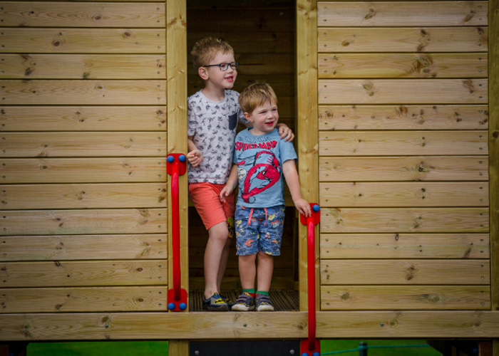 siblings playing together on a playground climbing frame