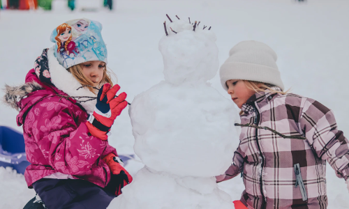 two sisters creating a snowman