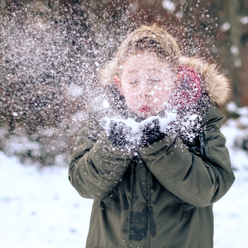 boy blowing on a handful of snow