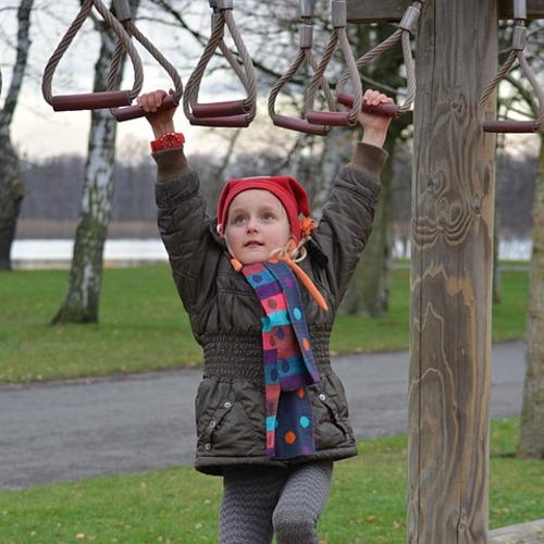 girl using playground monkey bars in winter