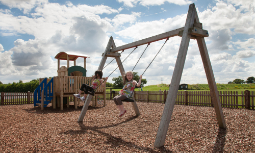two girls using playground swings