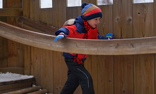 young boy using a playground in winter
