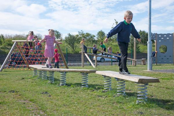 children using playground trim trail wobble boards