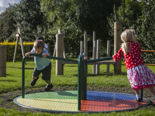 children using a playground roundabout