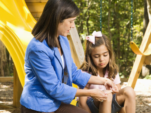 mum giving her daughter playground first aid