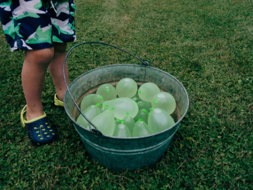 child with bucket of water balloons